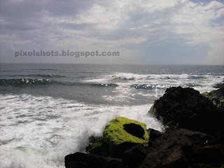 sea waves flowing over beach rocks,rough strong beach waves hitting sea side rocks,varkala waves and rocks photos
