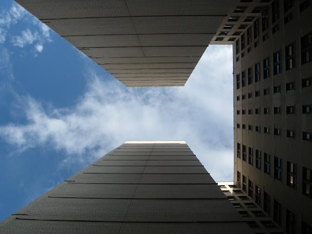 Looking straight up a big apartment building from a courtyard