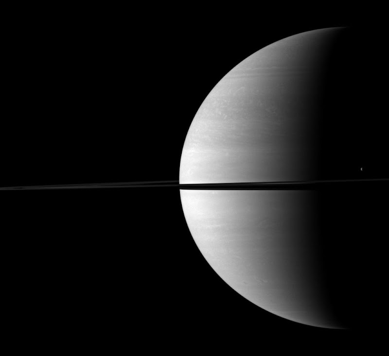 The moon Tethys stands out as a tiny crescent of light in front of the dark of Saturn's night side.