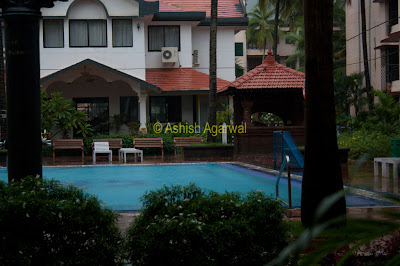 View of swimming pool and surrounding rooms at the Palmarinha Resort in Goa