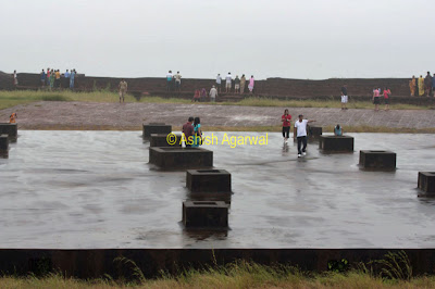 People wandering on the concrete platform in the middle of the Aguada fort in Goa