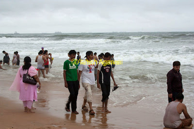 People wading in the shallow part of the Calangute beach in Goa.jpg