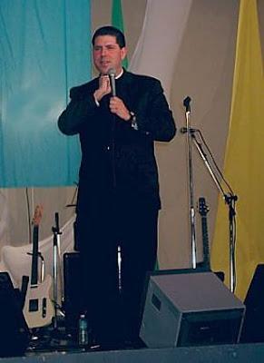 Padre Alberto Cutie de cuerpo entero con el micrófono en la mano