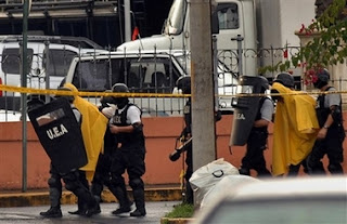 Costa Rican police escort a gunman and a hostage, both in yellow, after the gunman surrendered at the Russian Embassy in San Jose, Costa Rica, Friday May 11, 2007. A 20-year-old Kazakhstan native turned himself over to police on Friday, ending a three-hour standoff with police and safely releasing a man he had been holding at the Russian Embassy in Costa Rica, police said. The police did not confirm which of the two men was the hostage. (AP Photo)