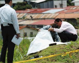 Police detectives observe the body of a murder victim that was found near the Tobias Bolanos Airport in San Jose, Costa Rica, August 20, 2008. Costa Rican authorities are trying to determine if four recent murder cases were commited by the same person. (Photo: Francisco Rodriguez/La Nacion)