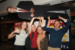 U.S. study abroad students, from left, Amanda Lawrence, 20, from Detroit, Michigan, Caitlain Kelly, 22, from San Francisco, California, Anna Rohde, 21, from South Dakota, Benjamin Weidman, 22, from New York, hold up a life-size poster of President-elect Barack Obama while celebrating in western San Jose. (Photo: Lindy Drew/Tico Times)