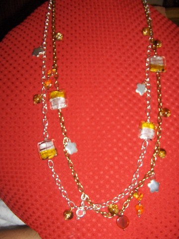Colar elaborado com varios tipos de correntes e contas em dourado e prateado com