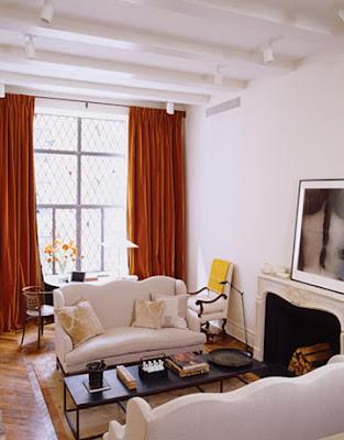 white living room with fireplace and dark orange velvet drapes