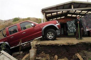 Un vecino barre su casa en Pelluhue, dañada tras un violento sismo que provocó olas que inundaron varias ciudades de norte a sur de Chile. Feb 28, 2010.