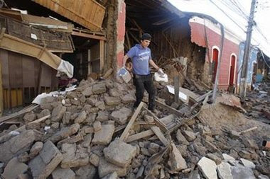 Un vecino de la localidad de Talca recupera algunas pertenencias de un edificio destruido por un devastador sismo que afectó el centro y sur de Chile.