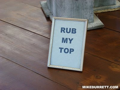 Framed sign says: RUB MY TOP