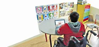 descrição: menino sentado em uma cadeira observa figuras afixadas em um painel à sua frente