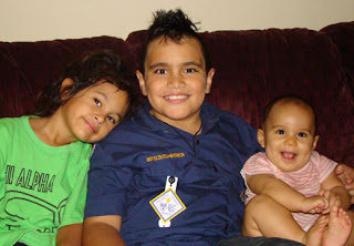 Malkolm with his little sisters, with his Boy Scout Uniform on, sporting a mohawk!