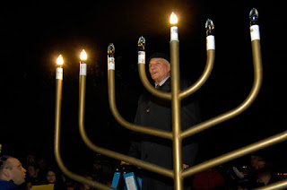 Rabbi Abraham Morhaim lights the Hanscom menorah. (U.S. Air Force photo by Mark Wyatt)