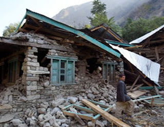 Photo: A man stands near the rubble of his house destroyed by an earthquake north of Srinagar, India, in October 2005. Photo: AP/Empics