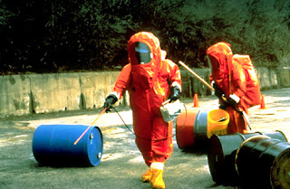 At EPA's hazardous materials training school, students go through field training on air monitoring and hazardous waste sampling. To protect against hazardous materials, personnel wear Level A personal protective clothing and equipment, which consists of a full-body, vapor-tight suit with a full face-piece or air respirator.