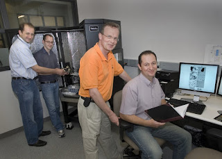(From left) Dmytro Nykypanchuk and Mathew Maye load a sample into an atomic force microscope while Daniel van der Lelie and Oleg Gang review data at Brookhaven Labs Center for Functional Nanomaterials.