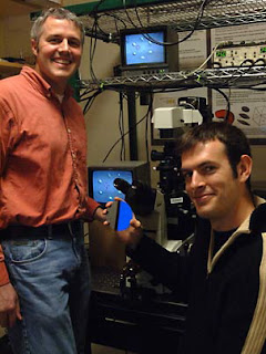 Mechanical and biological engineering professor Matthew Lang, left, and graduate student David Appleyard in the lab with equipment that shows how optical tweezers can be used to actively assemble tiny objects and cells on the surface of silicon wafers. Photo  Donna Coveney