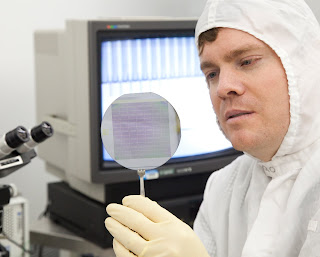 Hawkins holds a wafer of silicon