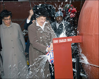 Bebe Drew Price breaks a champagne bottle against the USNS Charles Drew