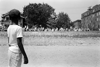 young African American boy watching a group of people