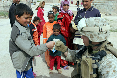 Sgt. Joseph S. Singleton plays with an Iraqi boy in Al Angur, Iraq. Al Angur, a town that American forces starting patrolling in October 2006, has opened its arms to the Coalition Forces. Soldiers from the 1st Iraqi Army Division patrolled alongside the soldiers and Marines assigned to the 2nd Combined Arms Battalion, 136th Infantry Regiment. U.S. Marine Corps photo by Cpl. Wayne Edmiston.