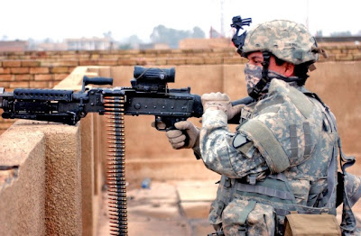 U.S. Army Pfc. Pedro Rangel provides security with an M240B machine gun from a rooftop while fellow soldiers begin work on building the new combat out post in Ghazaliya, Iraq, Jan. 14, 2007. Rangel is with Charlie Company, 2nd Battalion, 12th Cavalry Regiment, 1st Cavalry Division. U.S. Army photo by Sgt. Martin K. Newton.