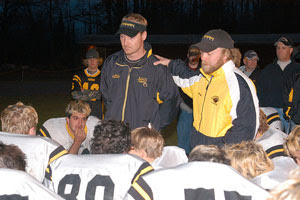 Cpl. James Hogan (center right, wearing baseball cap), a native of Superior, Wisc., speaks to the Northwestern High School Tigers football team, also of Superior, Wis., during his last season coaching in 2004. Hogan now serves with Company A, 4th Battalion, 31st Infantry Regiment, 2nd Brigade Combat Team, 10th Mountain Division (Light Infantry), out of Fort Drum, N.Y., and coaches Iraqi soldiers on infantry skills. Courtesy photo.