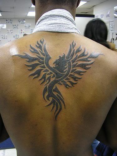 unicornio tatuaje. Aquí podemos ver que el tatuaje, ubicado en la espalda, presenta un circulo