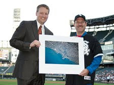 NASA astronaut Dr. John Grunsfeld presents a photo of Chicago from space to management at the White Sox game during the 2009 Hometown Heroes campaign in Chicago