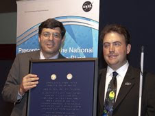 NASA Associate Administrator Chris Scolese, left, presented Mark Riccobono, executive director of the Jernigan Institute of the National Federation of the Blind a Braille-inscribed award with two Louis Braille Bicentennial Silver Dollars flown on Atlantis' STS-125 mission