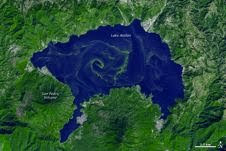 A large bloom of cyanobacteria spread across Guatemala's Lake Atitlán in green filaments, visible in this simulated-natural-color image from ASTER data taken Nov. 22, 2009