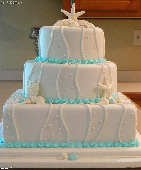 Stunning three tier white wedding cake with white seashells and tiffany blue