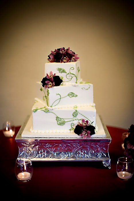 Elegant three tier square white wedding cake with green icing leaf patterns