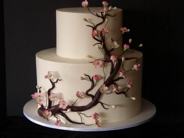 Gorgeous two tier round wedding cake in white with pink cherry blossoms