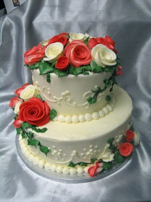 Pinkish red and white sugar roses on a two tier wedding cake
