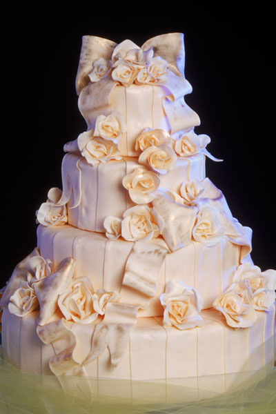 Extremely pale pink four tier round wedding cake with many gorgeous sugar