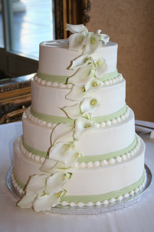 Simple three tier round white wedding cake decorated with green polka
