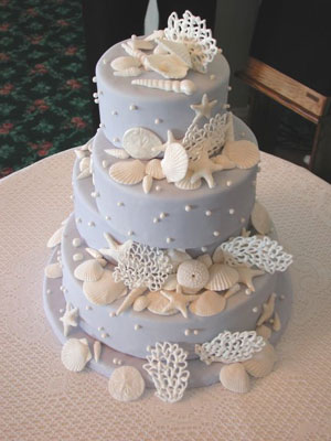 Light blue wedding cake with three round tiers and decorated with lovely sea