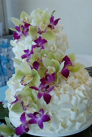 Three tier white chocolate shavings wedding cake decorated with purple