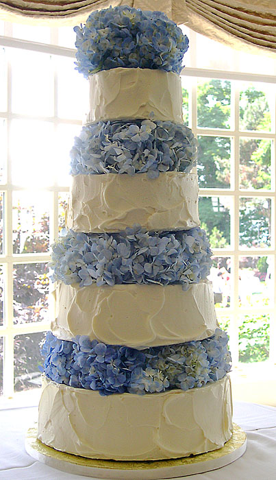 Four tier round white frosted wedding cake with bunches of blue hydrangeas