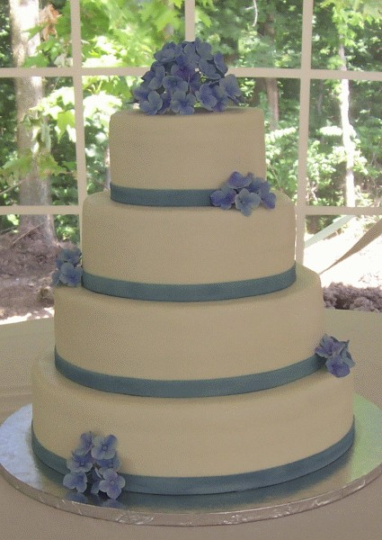 Four tier round wedding cake with pastel blue hydrangeas and pastel blue