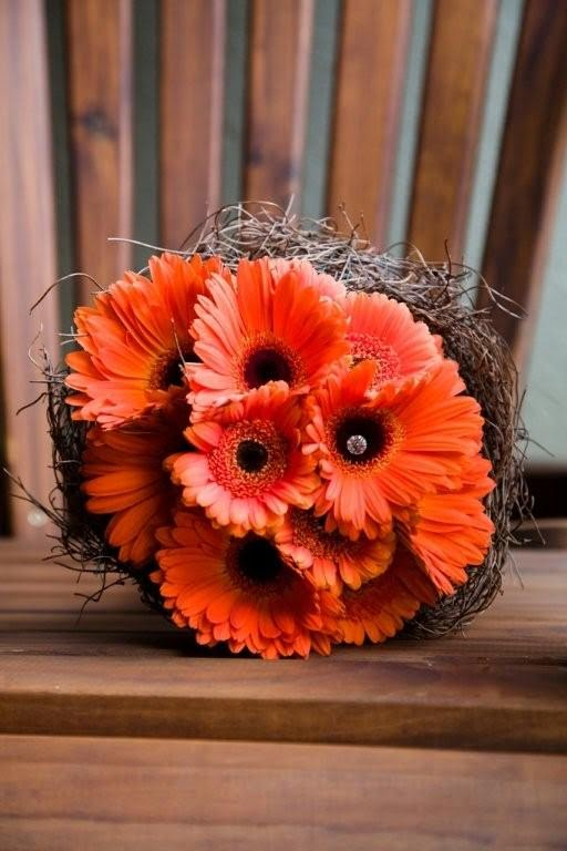 A lighter orange gerber daisy bouquet with orange roses