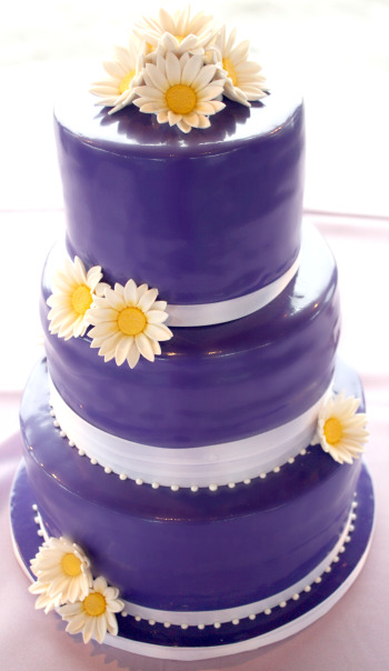 Three tier dark purple wedding cake with a glossy purple icing and white
