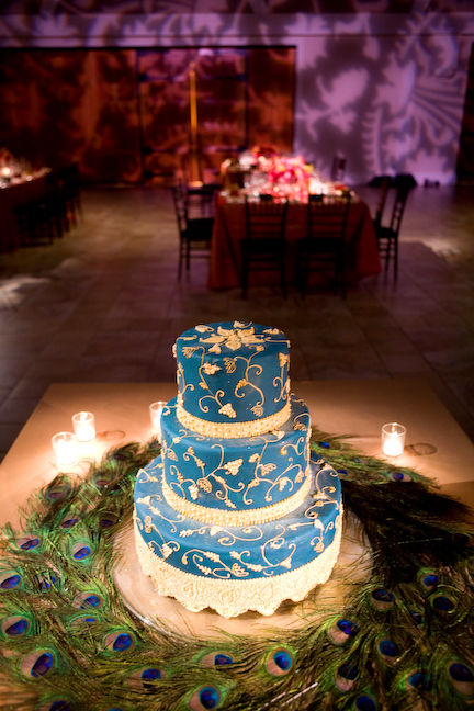 Blue wedding cake set over three tiers surrounded by beautiful peacock