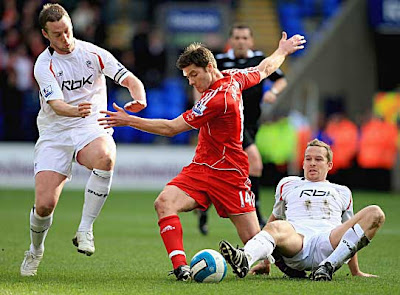 Xabi Alonso of Liverpool is challenged by Kevin Davies (right) and Kevin Nolan of Bolton.