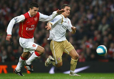 Robin Van Persie of Arsenal and Luke Young of Middlesbrough battle for the ball
