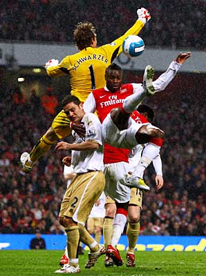 William Gallas of Arsenal jumps for the ball holding onto Luke Young