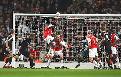 Emmanuel Adebayor of Arsenal (3L) scores his team's first goal against Liverpool in the first half.