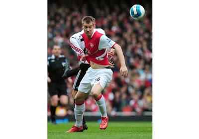 Nicklas Bendtner of Arsenal is held back by Jamie Carragher of Liverpool